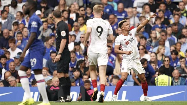 Sheffield United's Callum Robinson, right, celebrates scoring his side's first goal of the game during their English Premier League soccer match against Chelsea at Stamford Bridge, London, Saturday, Aug. 31, 2019. (John Walton/PA via AP)