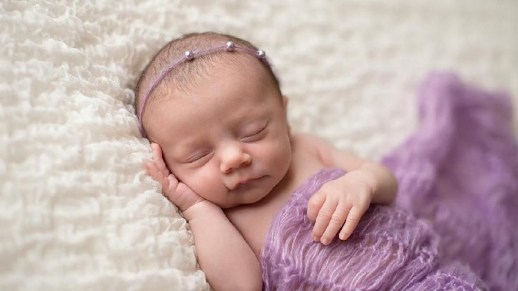 Sleeping, two week old newborn baby girl covered in a lavender purple blanket and wearing a pearl headband.