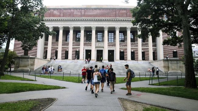 FILE - In this Aug. 13, 2019 file photo, students walk near the Widener Library in Harvard Yard at Harvard University in Cambridge, Mass. Ismail Ajjawi, 17, a Palestinian student who was denied entry to the United States just days before he was scheduled to start classes at Harvard University, has been admitted to the country. The university confirmed that Ajjawi was on campus as classes began Tuesday, Sept. 3, 2019. (AP Photo/Charles Krupa, File)