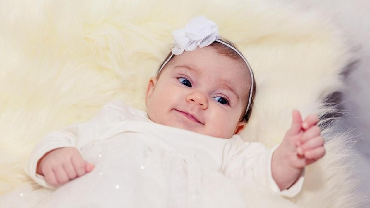 little baby on a light fur in white dress with a bow in the hair
