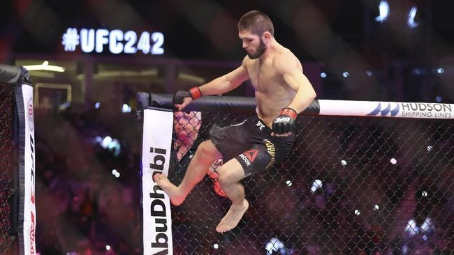 Russian UFC fighter Khabib Nurmagomedov, top, fights with UFC fighter Dustin Poirier, of Lafayette, La., during Lightweight title mixed martial arts bout at UFC 242, in Yas Mall in Abu Dhabi, United Arab Emirates, Saturday , Sept.7 2019. (AP Photo/ Mahmoud Khaled)