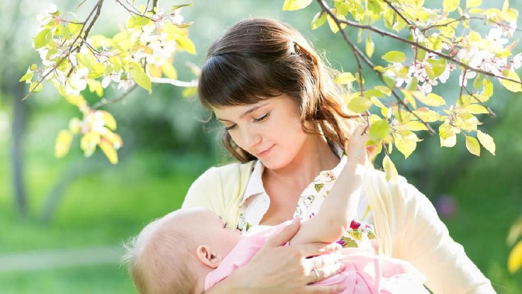 young mother breast feeding her baby girl in garden