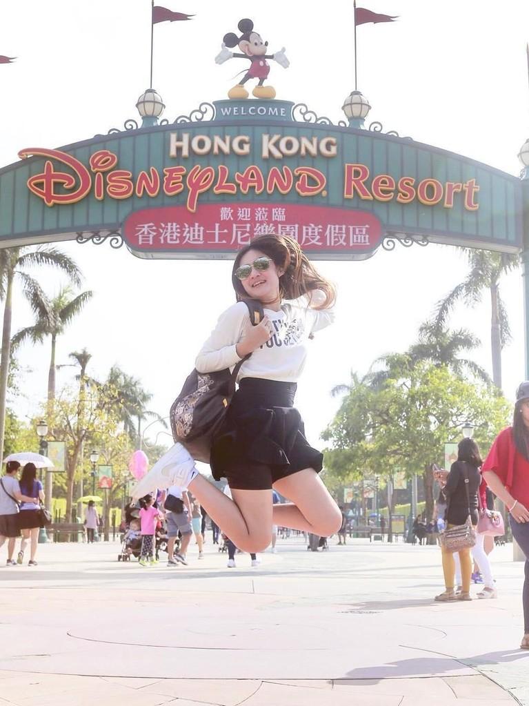 Nella Kharisma terlihat berpose di depan Disneyland Resort, Hongkong.