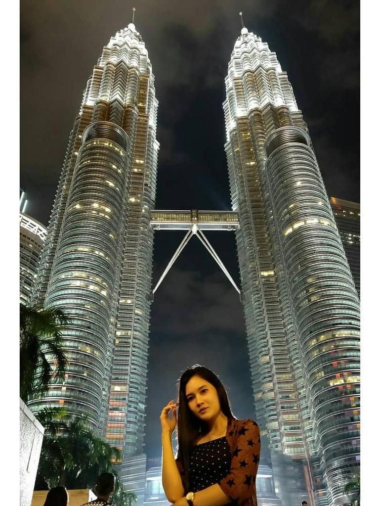 Gaya Nella Kharisma ketika sedang berpose di depan Twin Towers, Malaysia.