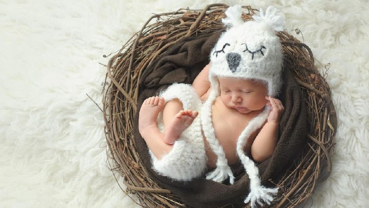 Three week old, newborn baby boy wearing a white, crocheted owl hat and shorts. He is sleeping on his back in a nest.
