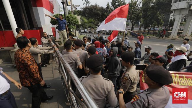 Massa memaksa masuk ke lobby Gedung KPK. Karena tak diperbolehkan, massa melempari gedung KPK dengan batu, botol hingga bambu.