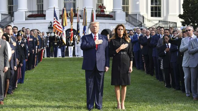 US President Donald Trump and First Lady Melania Trump observe a moment of silence on the South Lawn of the White House to mark the 18th anniversary of the 9/11 attacks, on September 11, 2019, in Washington, DC. (Photo by Nicholas Kamm / AFP)