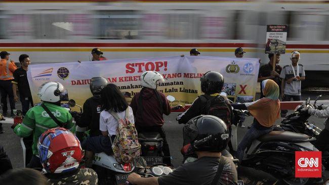 Polisi melakukan penilangan terhadap sejumlah pengendara penerobos pintu palang kereta di perlintasan sebidang di kawasan Bukit Duri Manggarai, Selasa (17/9).