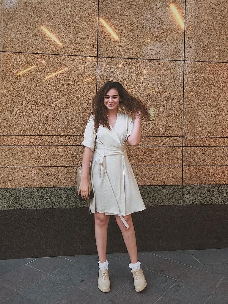 Mengenakan gaun putih, Sahila memadukannya dengan sepatu dengan warna yang senada.