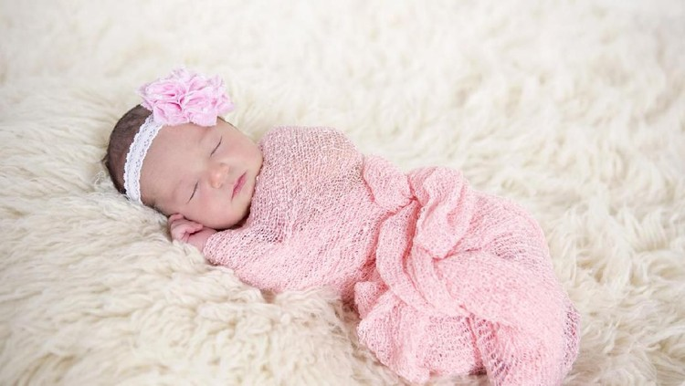 Beautiful five day old baby girl swaddled in a pink wrap and sleeping on a wool rug with pink flower headband.