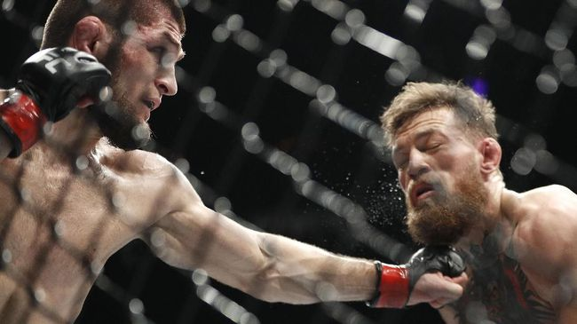 FILE - In this Oct. 6, 2018, file photo, Khabib Nurmagomedov, left, punches Conor McGregor during a lightweight title mixed martial arts bout at UFC 229 in Las Vegas. Nurmagomedov has not fought in the 11 months since he punctuated his star-making victory over McGregor at UFC 229 in Las Vegas by scaling the fence and jumping into the crowd to fight McGregor's entourage. (AP Photo/John Locher, File)