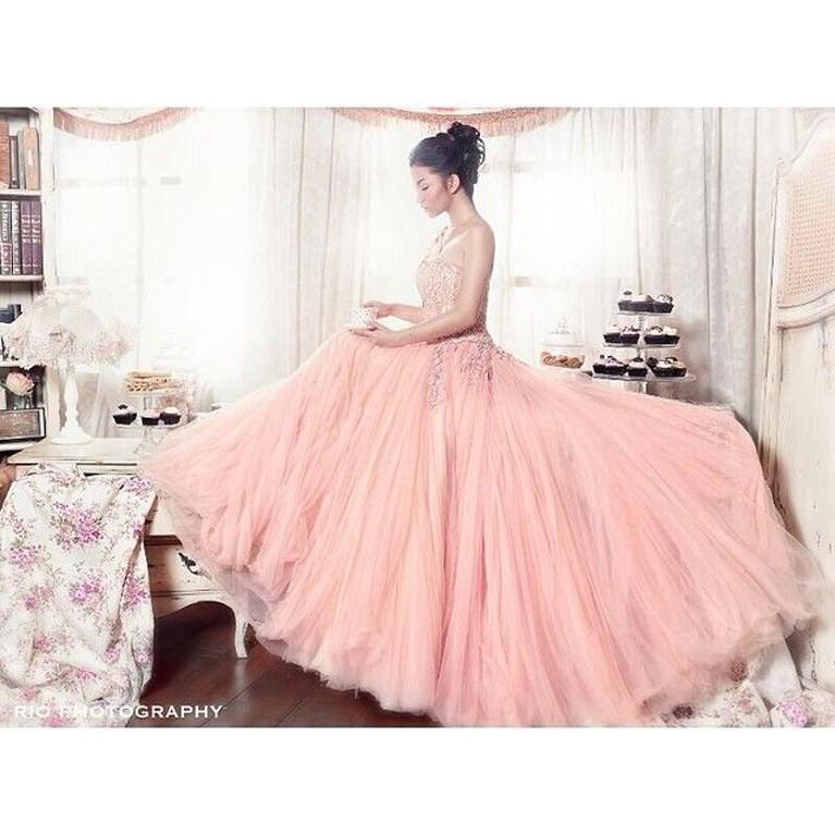 Ariel Tatum tampak menawan dalam sesi pemotretan mengenakan gaun panjang yang didominasi warna pink.
