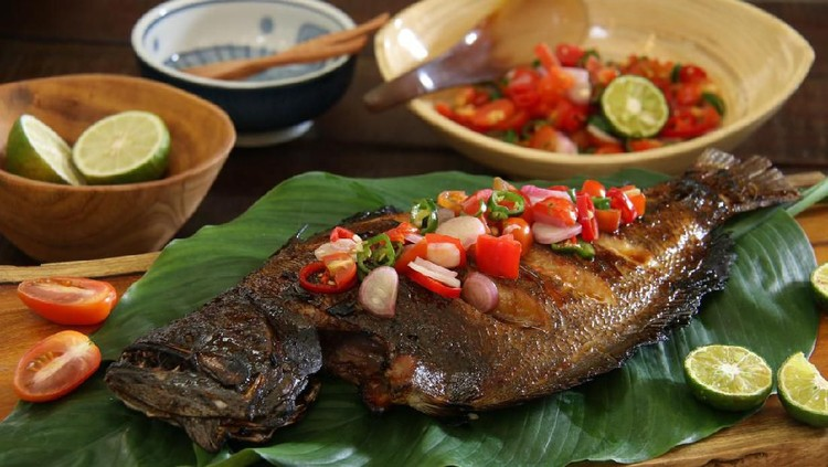 Ikan Bakar Dabu-Dabu, the popular grilled fish dish from Manado, North Sulawesi. The fish is lightly seasoned then grilled; served with the spicy tomato salsa. The fish is plated on a wooden serving block lined with layers of broad green leaves. Accompanied with extra salsa and limes.