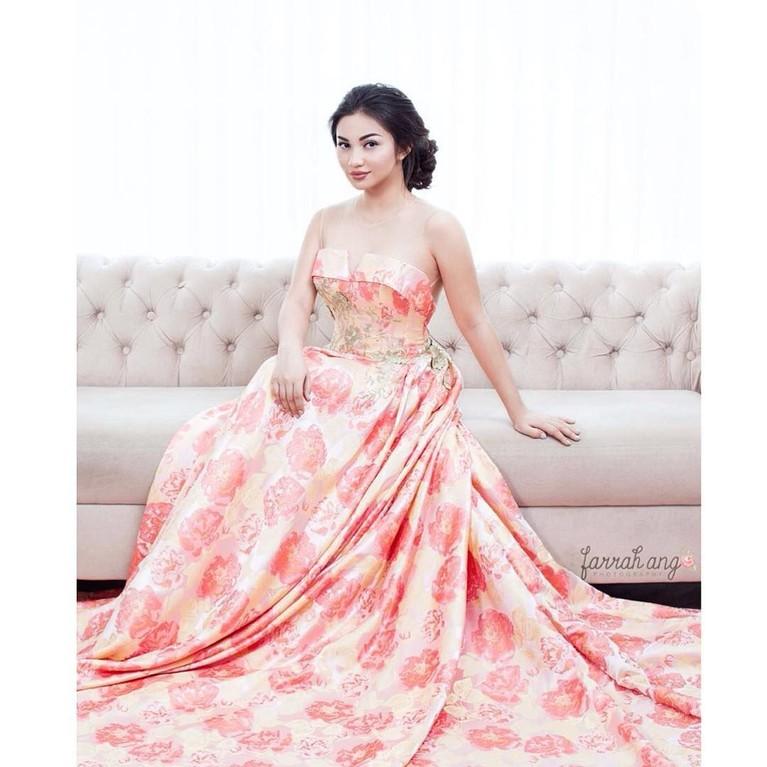 Ariel Tatum tampak berpose di atas sofa dengan gaun kombinasi merah dan pink.