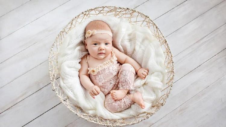 little newborn girl sleeps 1 month in a wattled basket