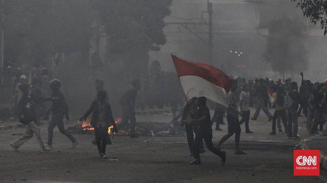 Seorang demonstran penolak RKUHP viral karena memegang bendera merah putih di tengah kepungan gas air mata. Polisi menetapkannya sebagai tersangka.