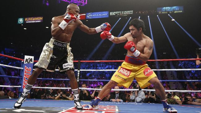 Floyd Mayweather Jr., and Manny Pacquiao (R) fight in a welterweight unification bout on May 2, 2015 at the MGM Grand Garden Arena in Las Vegas, Nevada. AFP PHOTO / JOHN GURZINKSI (Photo by JOHN GURZINSKI / AFP)