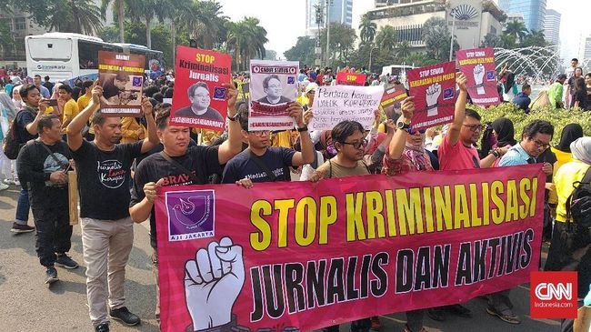Aliansi Jurnalis Independen (AJI) menggelar aksi jalan mundur di kawasan Car Free Day (CFD) di Bundaran Hotel Indonesia, Jakarta, Minggu (29/9). Mereka merespons keputusan Polda Metro Jaya menetapkan status tersangka untuk jurnalis Dandhy Dwi Laksono.