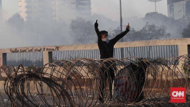 Polisi berupaya menghalangi massa dengan membuat barikade di jalan tol karena demonstran mendekat ke Gerbang DPR.