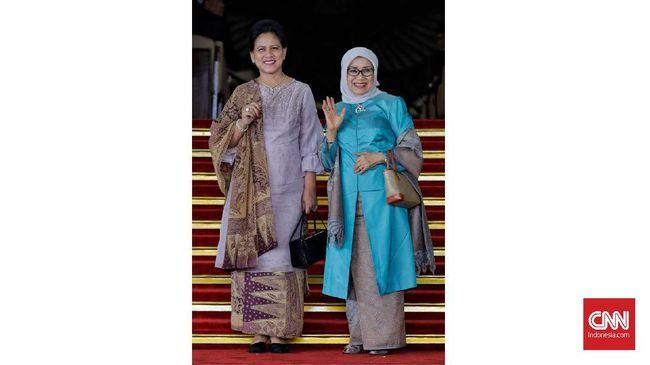 Iriana Jokowi terlihat bersahaja dengan padanan baju kurung ungu pucat dengan batik berwarna senada.
