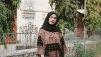 <p>Selebgram Dwi Handayani memilih atasan batik cokelat yang dipadu dengan kain berwarna senada. Ia melengkapi tampilannya dengan hijab dan <em>clutch bag</em> berwarna hitam. (Foto: Instagram @dwihandaanda)</p>