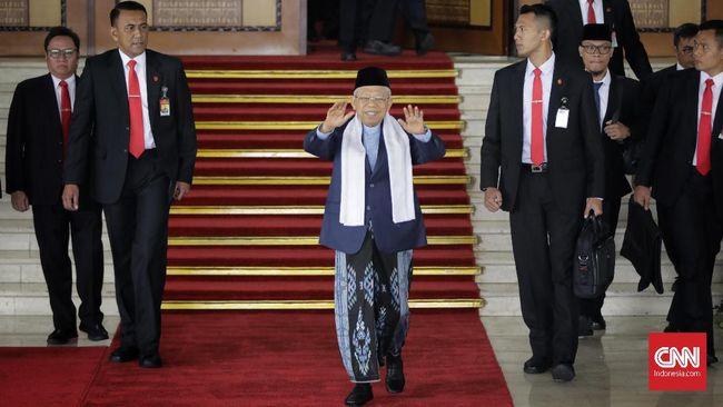 Ma'ruf Amin yang sempat mengenakan pakaian formal saat pelantikan, kini mengenakan pakaian 'kebesarannya': jas hitam dipadu sarung, syal putih, dan peci hitam.