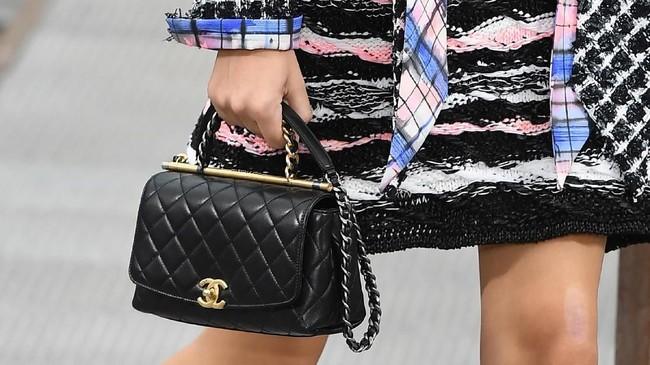 Microbag Chanel yang dipadukan dengan busana aneka warna dasar elegan Chanel masih terasa kuat dalam koleksinya. (Christophe ARCHAMBAULT / AFP)