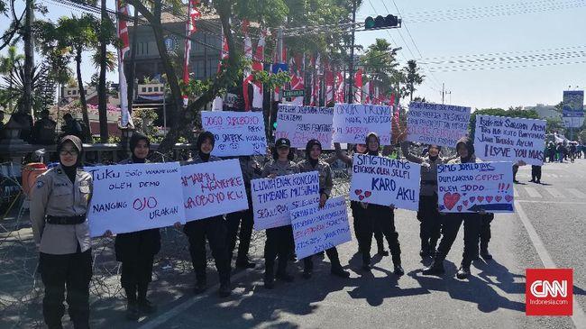 Sejumlah polwan menyambut kedatangan buruh dengan membentangkan poster-poseter bertuliskan