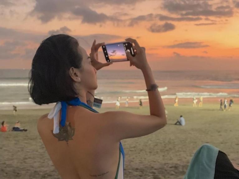 Momen saat Vanessa Angel menggunakan bikini di pinggir pantai sambil mengambil foto sunset. Ia juga menunjukan tato yang ada di punggung atas di bawah lehernya.