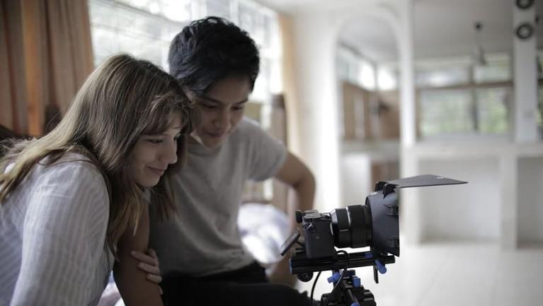 Foto ini memperlihatkan momen ketika Cassandra Lee dan Randy Martin menyaksikan video hasil syuting untuk video klip.