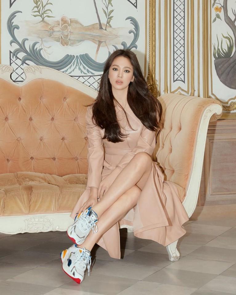 Foto selanjutnya menunjukan Song Hye Kyo yang feminim dan elegan. Ia tampil dengangaun berwarna coklat nude yang anggun. Penampilan Hye Kyo ini tetap mendapat sentuhan kasual karena memadukannya dengan sneakers.