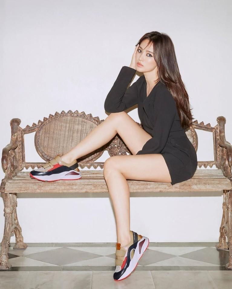 Foto selanjutnya mememperlihatkan Song Hye Kyo yang duduk di bangku. Dengan menggunakan mini dress hitam dan membiarkan rambut panjangnya terurai.