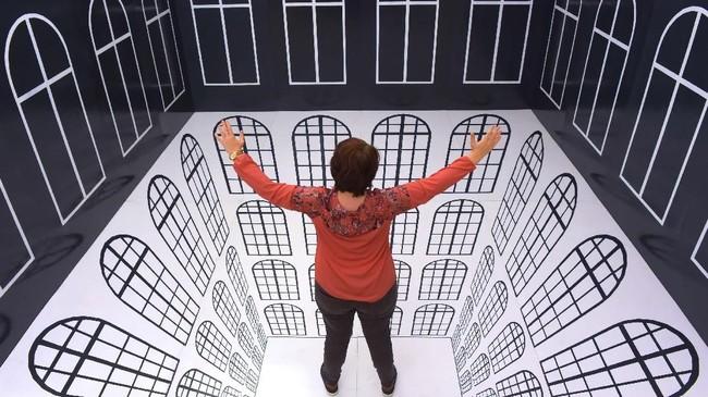 Seorang pengunjung menjajal ruang interaktif bernama 'Anamorphic Room'. (AP Photo/Jens Meyer)