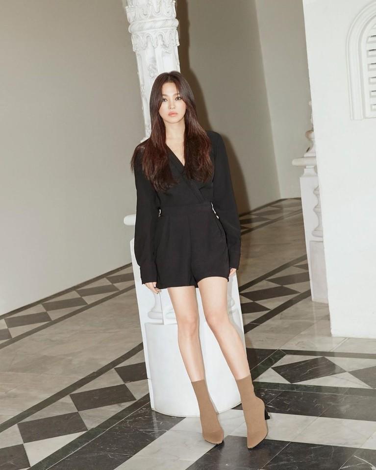 Di foto lain, ia memadukan mini dress hitamnya denganankle boots heelsberwarna coklat. Penampilan ini membuat tubuhnya terlihat lebih jenjang.