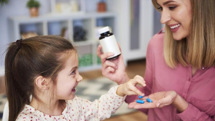 Young mum giving her little daughter the medicine