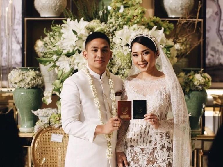 Tampak dengan senyum bahagia, keduanya memamerkan buku nikah setelah proses akad.