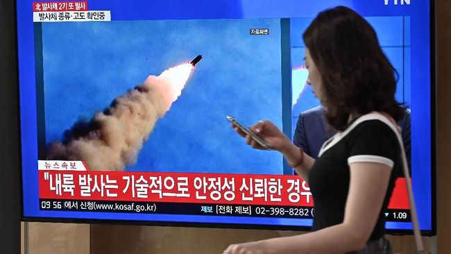A woman walks past a television news screen showing file footage of a North Korean missile launch, at a railway station in Seoul on September 10, 2019. - North Korea on September 10 fired projectiles toward the sea, South Korea's military said, hours after Pyongyang said it is willing to hold working-level talks with the United States in late September. (Photo by Jung Yeon-je / AFP)