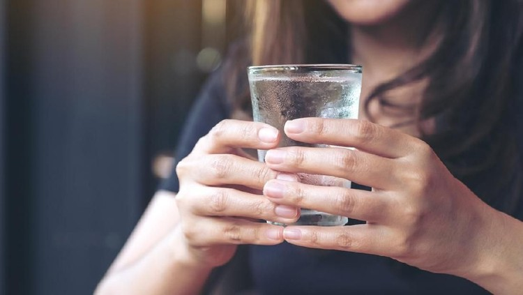 Closeup image of woman holding a glass of cold water to drink