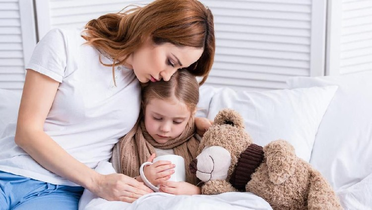 mother taking care of sick daughter and hugging her in bedroom