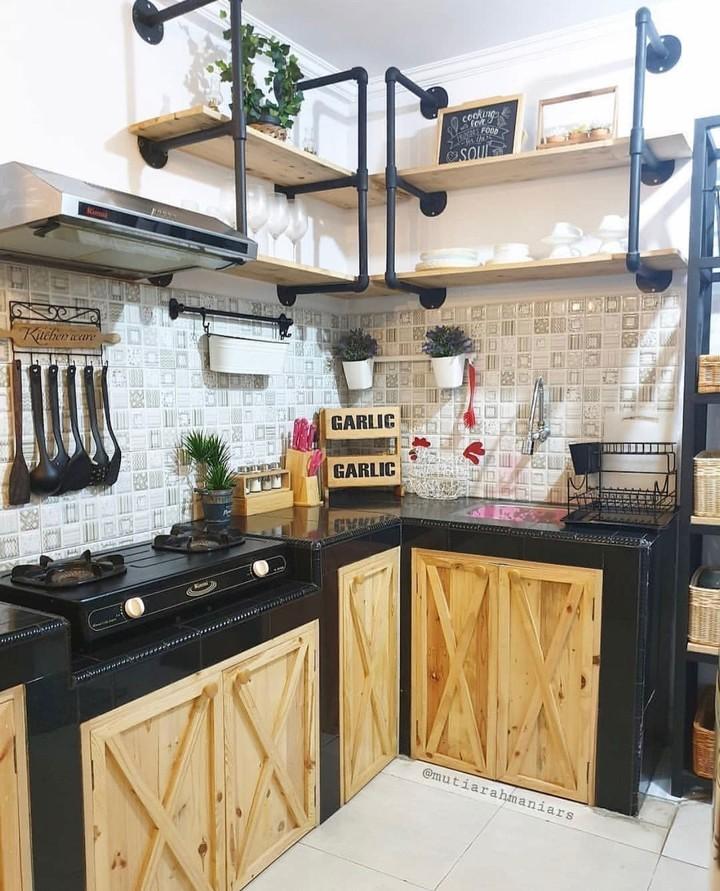 <p>Dapur dengan warna cokelat dan hitam ini terlihat keren dan tidak terlalu feminin. Pemilik juga menggunakan rak gantung bersusun untuk menyimpan dekorasi. (Foto: Instagram @dekorasidapur)</p>