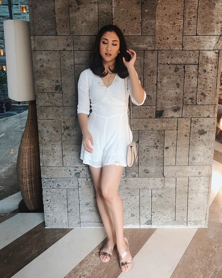 Sherina berpose dengan baju terusan berwarna putihnya dilengkapi dengan flat shoes dan tas tangan kecil warna krem.