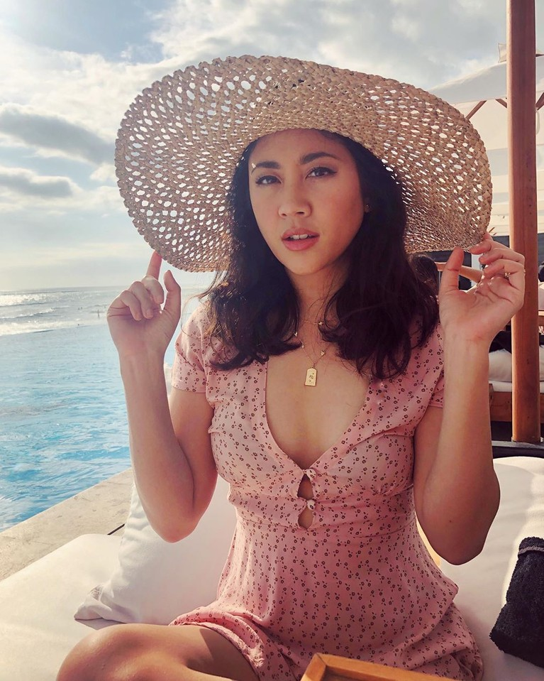 Wanita itu masih mencuri perhatian dengan menggunakan atasan berwarna pink dengan corak warna hitam dan topi pantai lebar sedang duduk di pinggir kolam.