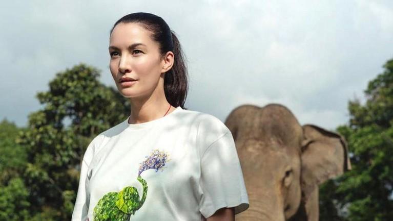 Nadya Hutagalung terlihat sedang foto bersama seekor gajah di belakangnya.
