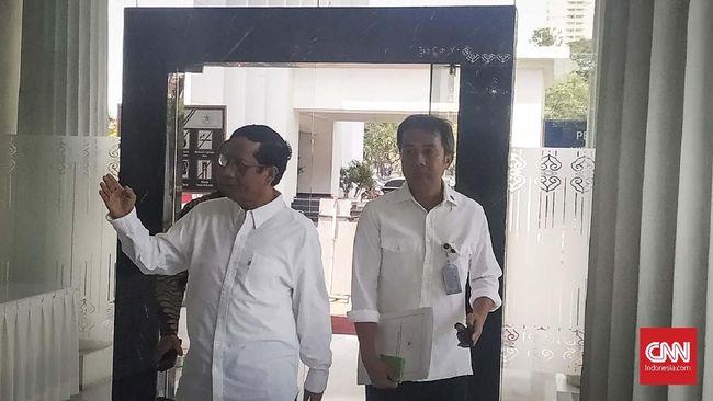 Mengenakan kemeja putih, mantan Ketua MK Mahfud MD menyambangi Istana Negara pagi ini setelah mendapat telepon pukul 00.20 WIB.