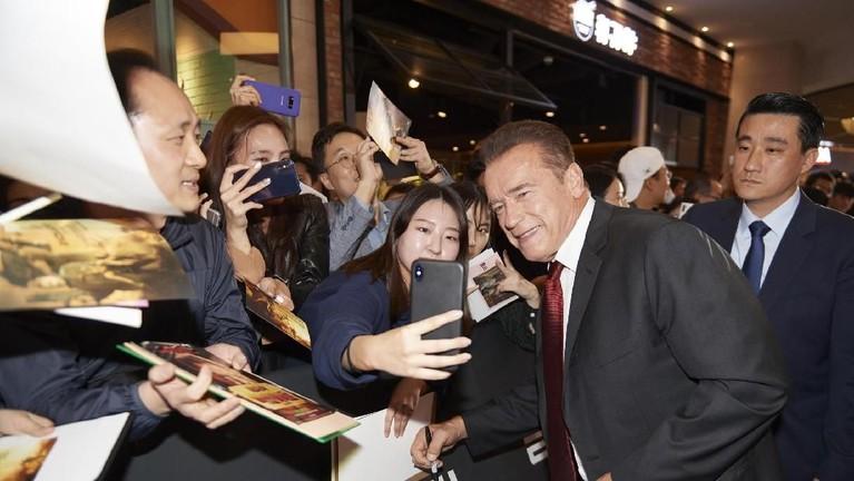 Arnold Schwarzenegger juga tak ketinggalan meremia ajakan penggemar untuk berswafoto.
