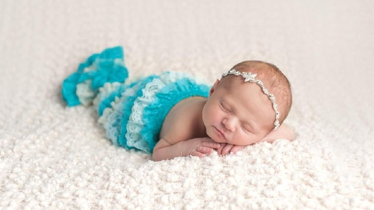 A sleeping, ten day old newborn baby girl wearing a lace aqua blue mermaid tail. She is lying on her stomach on a cream colored, bouncle blanket.