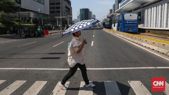 Warga Jakarta menggunakan payung menghalau sengatan matahari siang hari di kawasan Thamrin, Jakarta, Selasa, 22 Oktober 2019. BMKG mencatat suhu udara pada siang hari masih terjadi di sekitar wilayah Indonesia bagian selatan hingga akhir Oktober 2019. CNNIndomesia/Safir Makki
