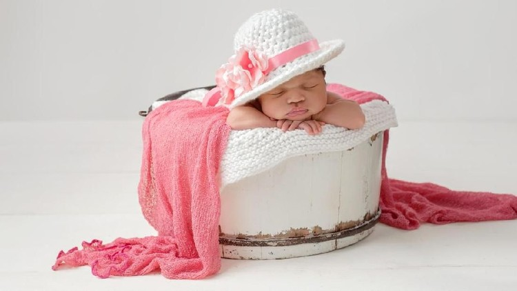 A portrait of a three week old, sleeping, newborn, baby girl wearing a fancy, brimmed Easter hat with pink flowers. She is sleeping in a vintage, white, wooden bucket.