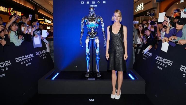Mackenzie Davis yang berperan sebagai Grace terlihat berpose di sebelah replika robot terminator.