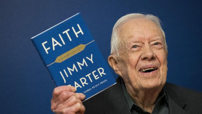 NEW YORK, NY - MARCH 26: Former U.S. President Jimmy Carter holds up a copy of his new book 'Faith: A Journey For All' at a book signing event at Barnes & Noble bookstore in Midtown Manhattan, March 26, 2018 in New York City. Carter, 93, has been a prolific author since leaving office in 1981, publishing dozens of books.   Drew Angerer/Getty Images/AFP